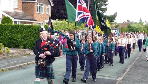 Scottish Piper Reg Flower leads the procession through Wistaston