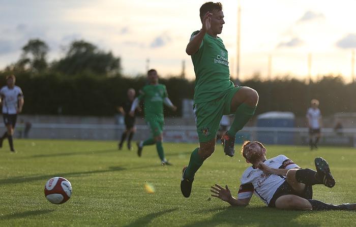 A Nantwich player rides a tackle