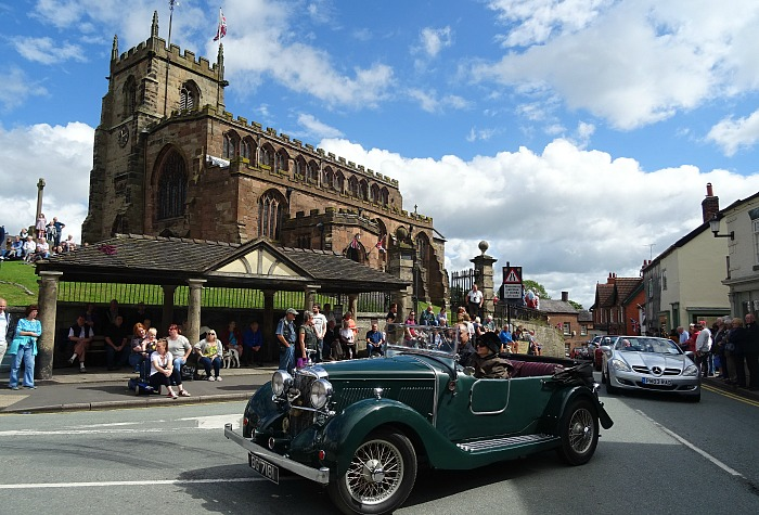 transport festival in Audlem - An Alvis in the parade passes St James Church