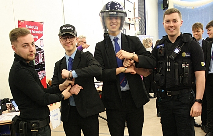 Ash Wood and Dan Owen from Cheshire Police give Harry Hassall and David Wright the experience of being handcuffed