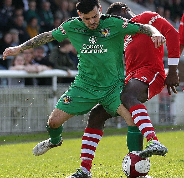 Assistant Manager-player Danny Griggs fights for the ball