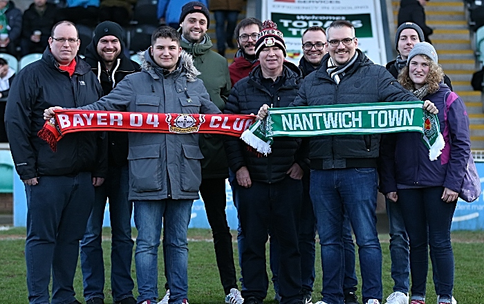 Half-time - Nantwich Town Press Officer Ryan Batty exchanges club scarves with Bayer 04 Leverkusen fans (1)