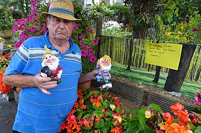 Laurence Perry with two gnomes ripped from their base and the now empty wooden shelf at the front of his garden (1)