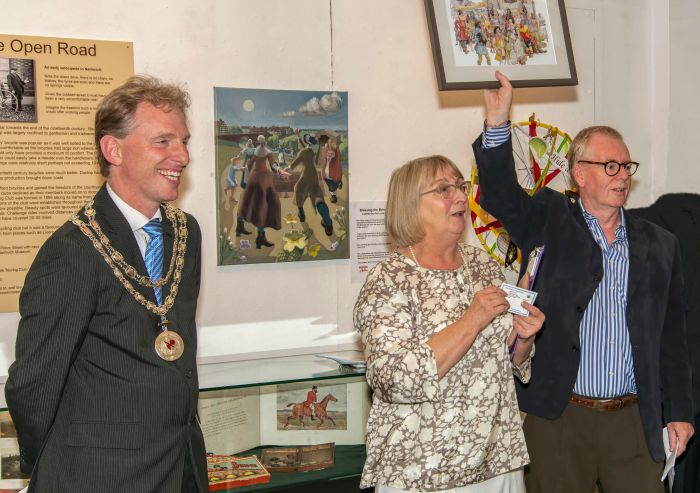 Mayor of Nantwich Town Council, Councillor Andrew Martin looks on as the museum's Molly Stone and Nick Dyer introduce the exhibition raffle