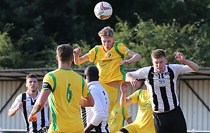 Nantwich player rises the highest to win the ball