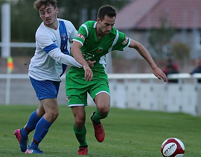 Nathan Cotterall is held back by a Sandbach United player