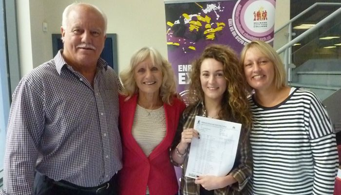 Olivia Moorcroft celebrating her  GCSE results with members of staff and a Governor of Malbank
