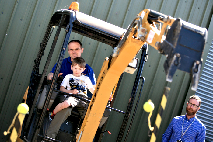Owen Hughes, 5, and Dad Duncan attempt to knock the tennis balls off, on the digger (1)