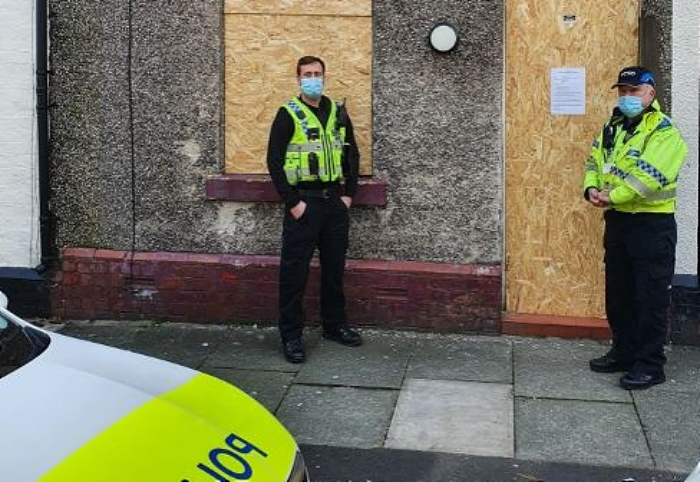 county lines - PC Ian Harrison, left, and PCSO Stephen Marnick outside the house in Bower Street, Widnes, that has been closed for three months (1)