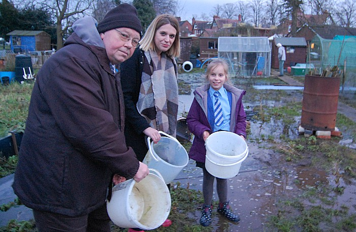 Allotments chair Phil Williams, MP Laura Smith, and young gardener Lottie Nichols, 9
