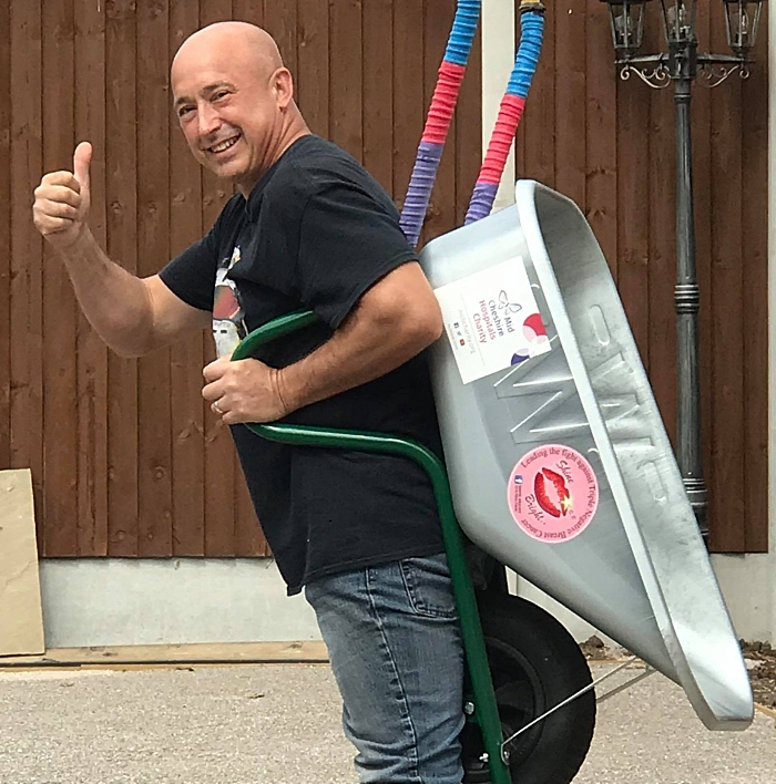 Roy Price practices carrying a wheelbarrow in readiness for his walk up Snowdon (1)