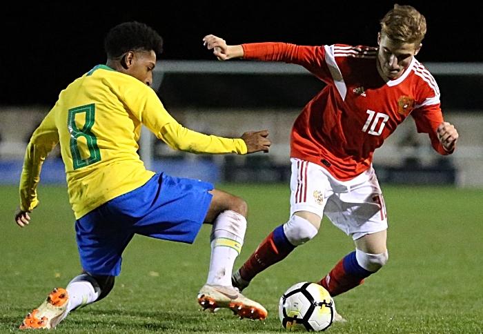 Russias Petrov Maksim controls the ball under pressure from Brazils Talles Macedo Toledo Costa