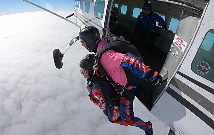 Sarah Iggo exits the plane with instructor for her tandem skydives