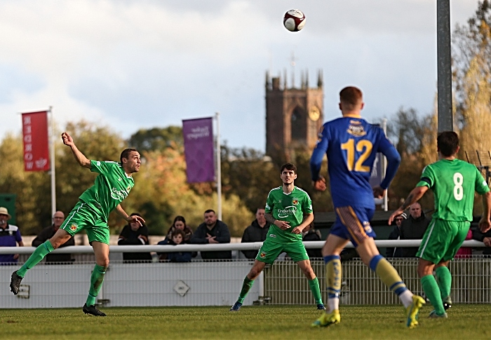 Second-half - Joe Stair heads the ball forwards with St Mary's Church, Nantwich in the background (1)