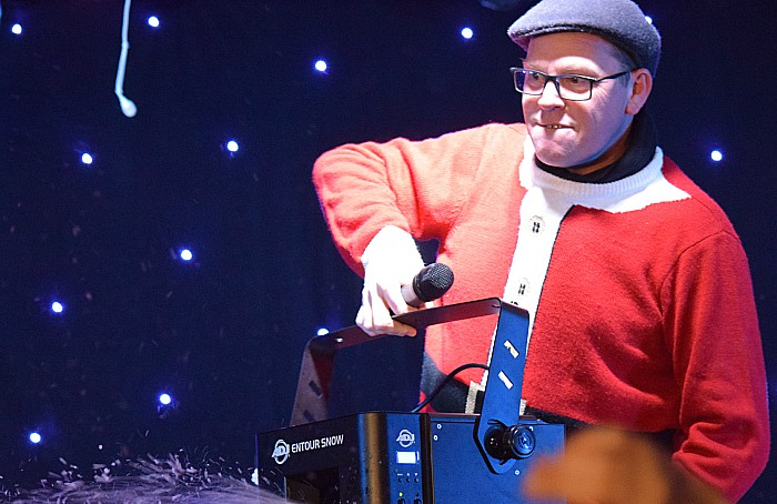 Silk 106.9 compere gives the crowd some snow from a snow machine