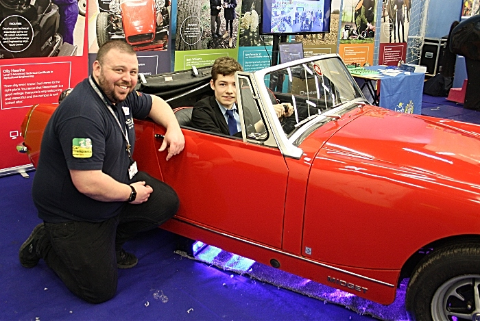 Careers - Simon Bishop is happy to be allowed to sit in the driving seat of a renovated 'Midget' as the process was explained to him by John Brookfield from Reaseheath College Motor Vehicle department