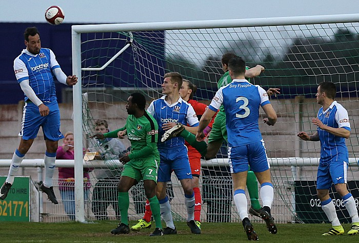 Stalybridge Celtic head the ball clear
