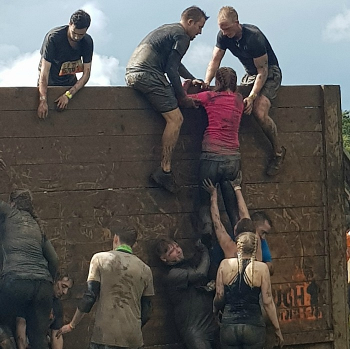 The Hibberts solicitors team helping one another over the obstacles