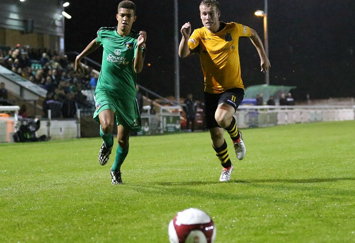 Troy Bourne sprints for the ball with Marine midfielder James Edgar