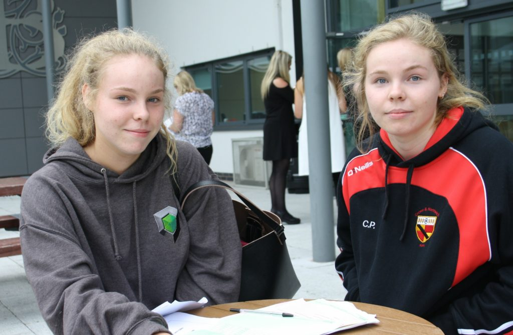 Twins, Anna and Charlotte Harding sit and assess their results