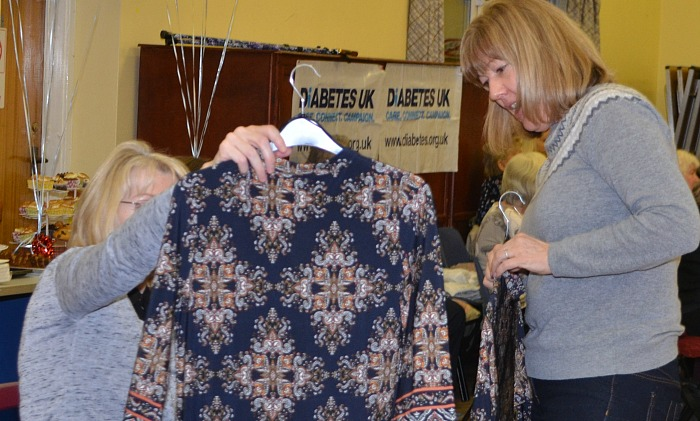 Wistaston Rose Queens Fashion Show and Sale - a garment is inspected