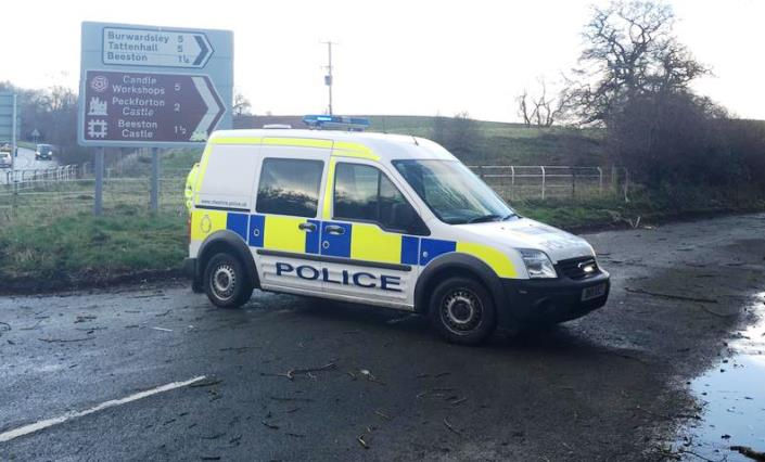 police car at closed lane with tree blown down by strong winds