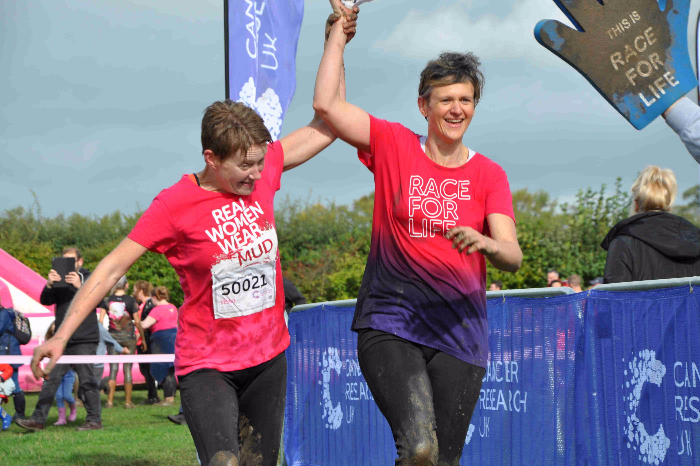 runners in pretty muddy sea of pink event